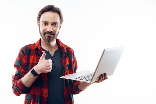 Happy guy holding laptop and shows thumbs up