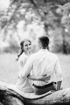 白いシャツを着た幸せな男とターコイズブルーのドレスを着た女性が森の公園を歩いています