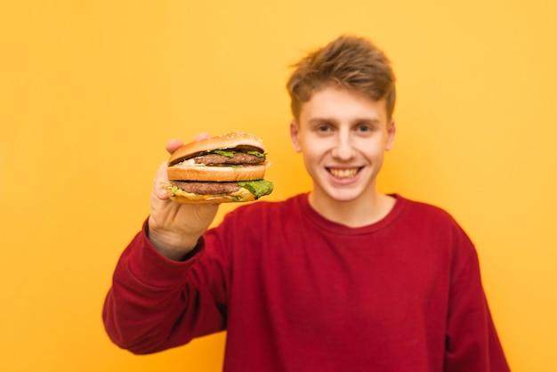 Счастливый парень в повседневной одежде держит в руках аппетитный бургер