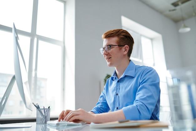 Счастливый парень в официальной одежде смотрит на экран компьютера во время поиска в сети за столом
