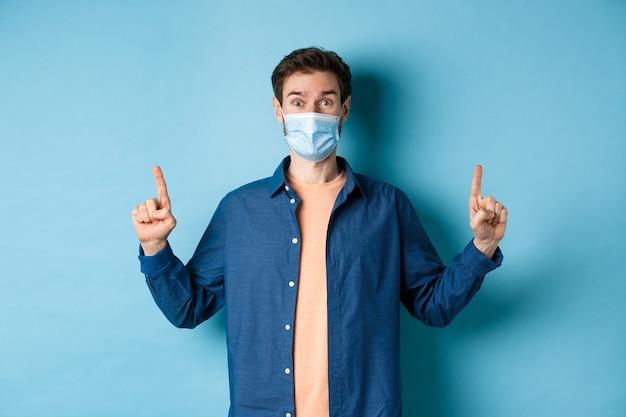 Счастливый парень в медицинской маске взволнован хорошими новостями