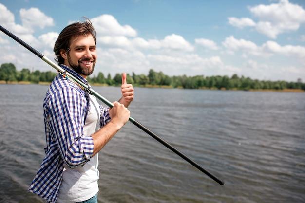 幸せな男は川の近くに立って見ています。彼は笑っている。ガイは右手を右肩につけて釣竿を持っています。また、男は上向きです。彼は幸せそうに見えます。