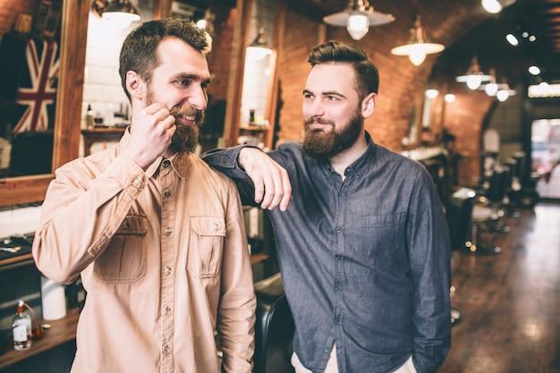 Счастливый парень трогает его новые усы своими руками. его друг рад видеть его таким. он улыбается ему.