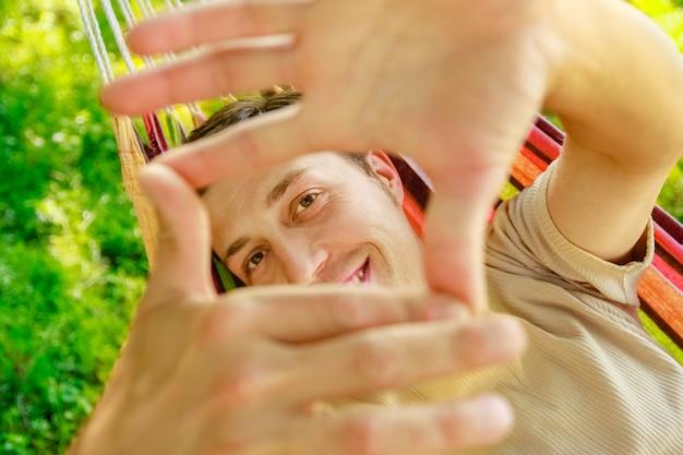 自然公園のハンモックで幸せな男