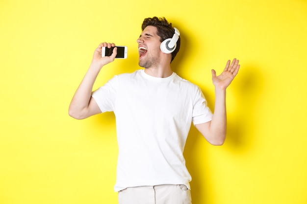 Happy guy playing karaoke app in headphones, singing into smartphone microphone, standing over yellow background.
