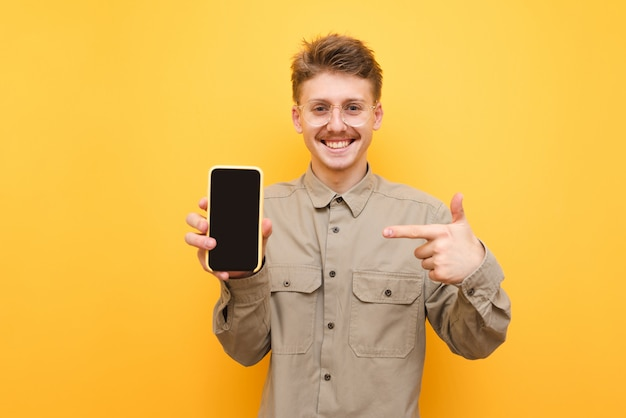 Happy guy in shirt and glasses is pointing finger at smartphone with black screen