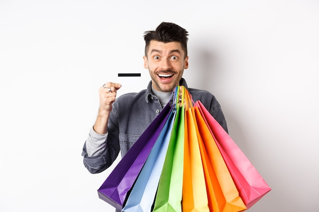 Happy guy shopaholic holding colorful shopping bags and showing plastic credit card, smiling excited, standing white background.