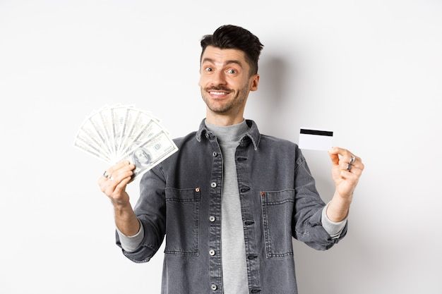 Happy guy showing plastic credit card and dollar bills, giving choice, standing on white background.