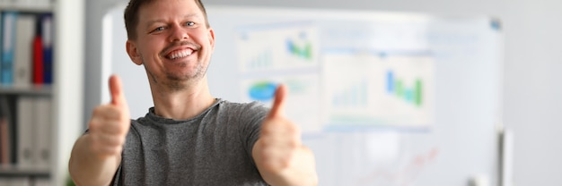 Happy guy stands in office and shows ok gesture