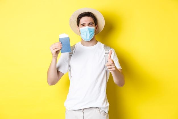 Счастливый парень-турист в медицинской маске показывает паспорт с билетами на отпуск, подмигивает и указывает вперед, желтая стена