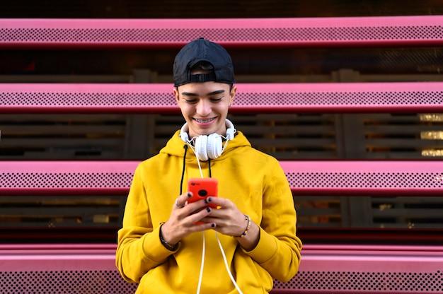 Счастливый парень, используя смартфон для прослушивания музыки в наушниках