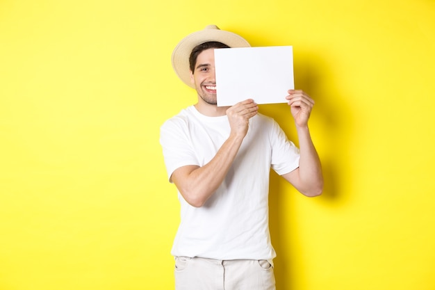 Happy guy on vacation showing blank piece of paper for your logo, holding sign near face and smiling, standing against yellow background.