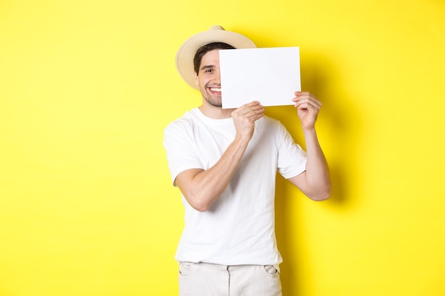 Happy guy on vacation showing blank piece of paper for your logo, holding sign near face and smiling, standing against yellow wall
