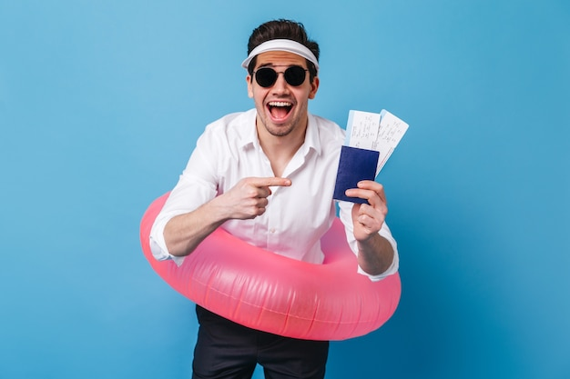 Ragazzo felice in camicia bianca e pantaloni scuri pone con cerchio gonfiabile, documenti e biglietti. ritratto di uomo in bicchieri e cappello su uno spazio blu.