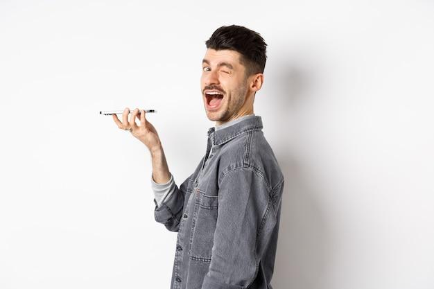 음성 번역기 응용 프로그램을 사용하거나 스피커폰에 말하는 동안 카메라를보고 윙크하는 행복한 사람, 흰색 배경에 서있는 입 가까이 전화를 들고.