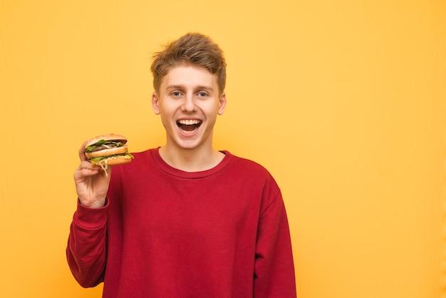 食欲をそそるハンバーガーを手に持った幸せな男が黄色の上に立つ