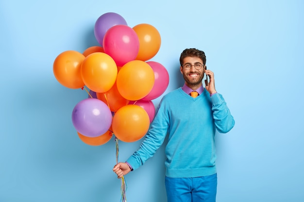 파란색 스웨터에 포즈 풍선과 함께 행복 한 사람