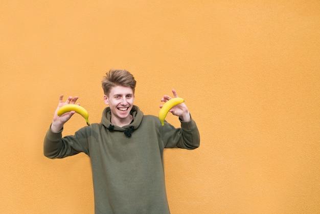 Счастливый парень с бананами в руках стоит на оранжевой стене