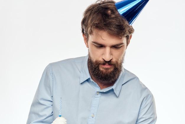 バースデーケーキの白い背景のコンパクトな企業パーティーのトリミングされたひげのビューを持つ幸せな男 Premium写真