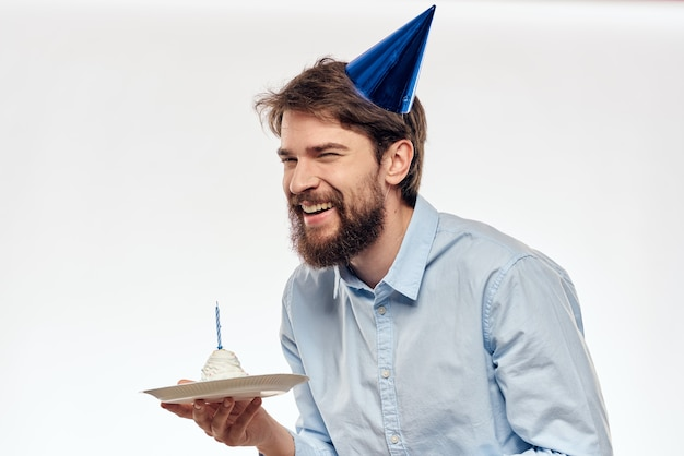 Happy guy with birthday cake on white wall