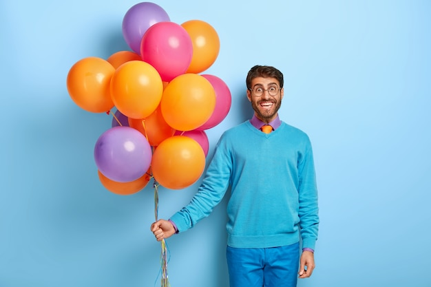 Happy guy with birthday hat and balloons posing in blue sweater