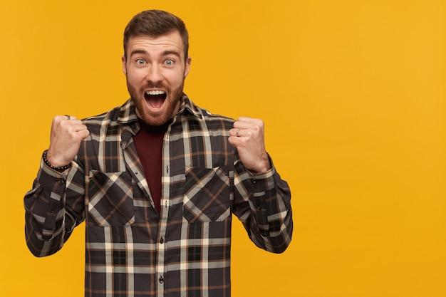 갈색 머리와 수염을 가진 행복 한 남자입니다. 체크 무늬 셔츠와 액세서리 착용. 주먹을 움켜 쥔다. 성공에 흥분합니다. 오른쪽에 공간 복사, 노란색 벽 위에 절연