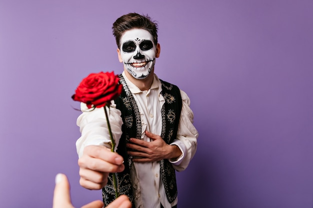 Happy guy with joyful look is grateful and gives rose to his beloved person. indoor portrait of man with halloween makeup.