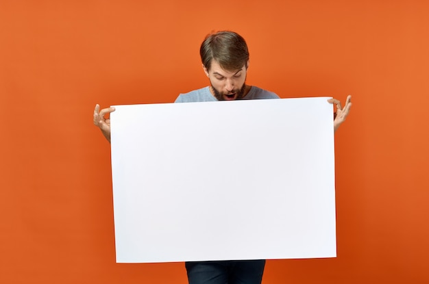 Happy guy with mockup in hand poster orange background copy space. high quality photo