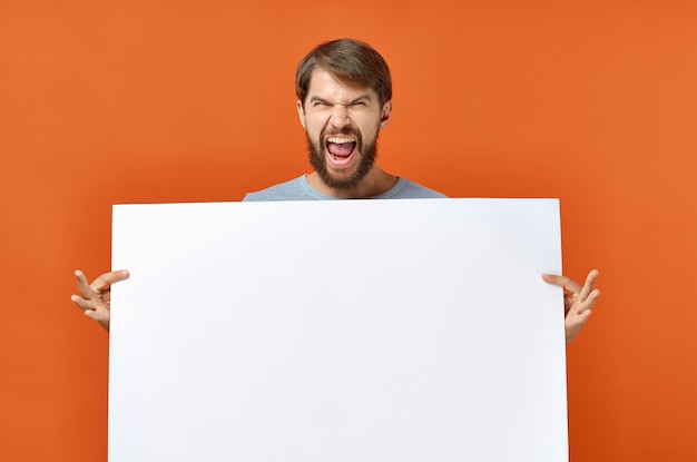 Happy guy with mockup in hand poster orange background copy space.
