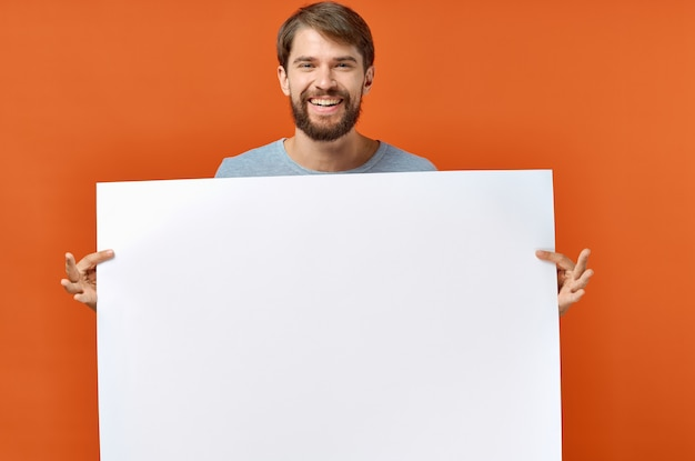 Happy guy with mockup in hand poster orange background