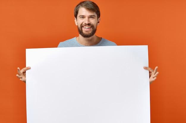 Счастливый парень с макетом в руке плакат оранжевый фон