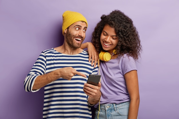 Happy guy in yellow hat and striped jumper, explains to afro girl how to use new application at smartphone, points in display, stand closely, cannot imagine life without modern technologies.
