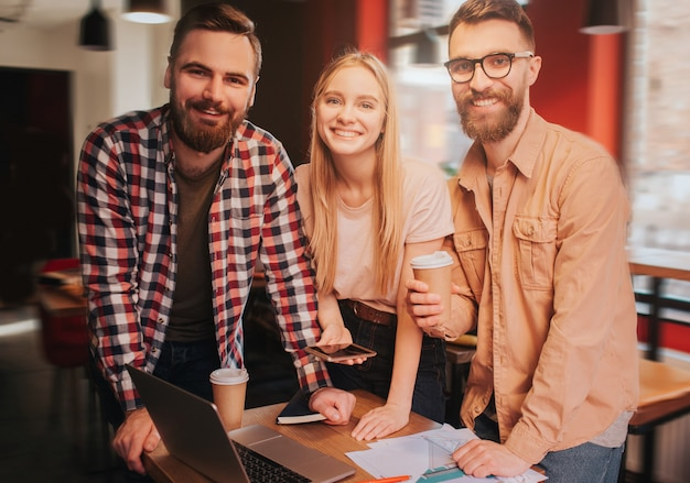 Happy guys and girl are standing near table with business materials and looking straight forward. they are smiling.