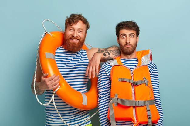 Счастливые парни позируют на пляже со спасательным жилетом и спасательным кругом