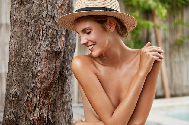 Happy half nude woman with healthy skin, looks happily, wears straw hat, poses near trunk of tree, satisfied with spa or beauty procedure. cheerful young female with bare body
