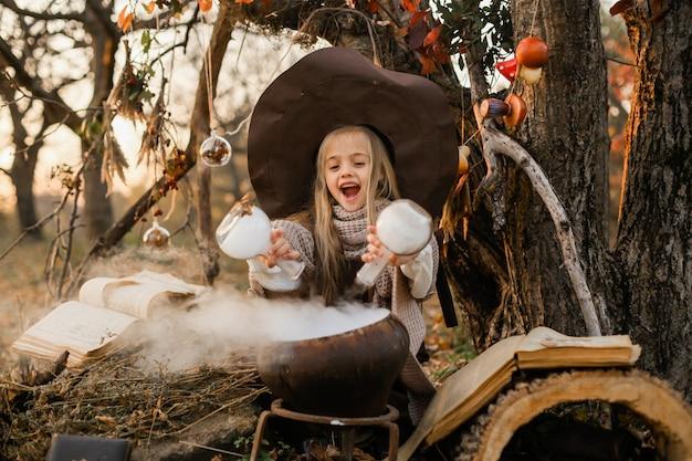 Счастливого хэллоуина. милая девушка в костюме ведьмы находится в логове ведьмы. милая веселая маленькая ведьма варит волшебное зелье. хэллоуин.