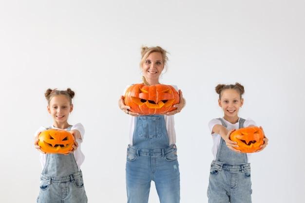 Счастливого хэллоуина и праздников концепция - мать и ее дочери с тыквами. счастливая семья готовится к хэллоуину.