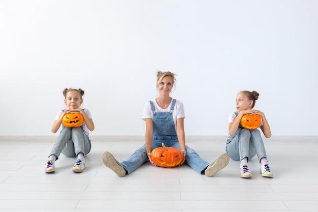 幸せなハロウィーンと休日の概念-カボチャを持つ母と彼女の娘。ハロウィーンの準備をしている幸せな家族。