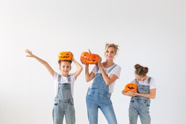 幸せなハロウィーンと休日の概念-カボチャを持つ母と彼女の娘。幸せな家族