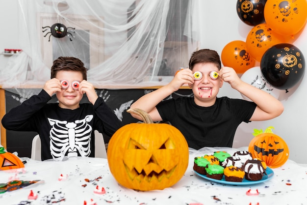 Happy halloween! attractive young boy with his big brother are preparing for halloween party. brothers in costumes are having fun and playing with scary eyes decoration