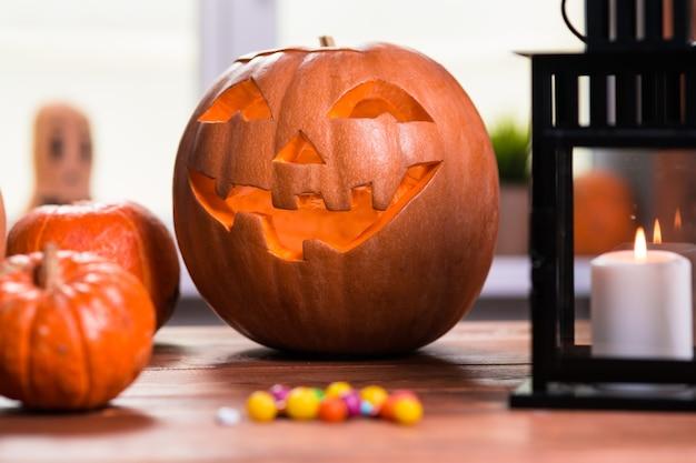 Счастливого хэллоуина. фон перед окном с тыквами, фонарем, пауками и другими символами страшного праздника