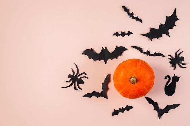 Счастливого хэллоуина. летучие мыши и тыква на розовом пастельном фоне. место для текста.