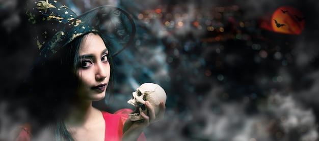 ハッピーハロウィン。美しい女性の衣装と頭蓋骨を保持しています。暗い背景にスペースをコピーします。