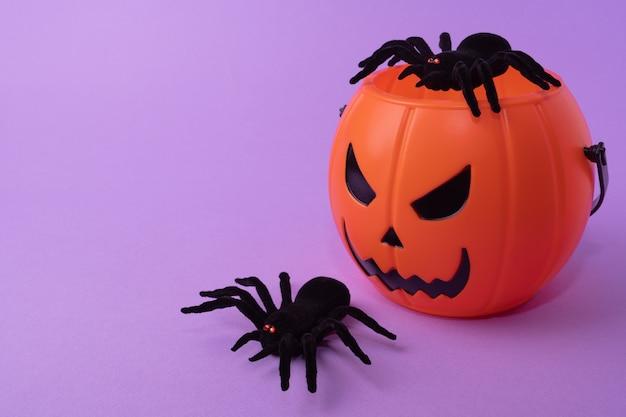 Happy halloween concept halloween pumpkin bucket with black spiders on a purple background