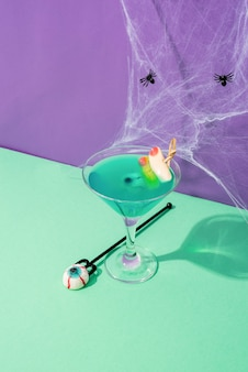 해피 할로윈 개념입니다. 보라색 배경에 파티 장식이 있는 무서운 화려한 보라색 할로윈 칵테일
