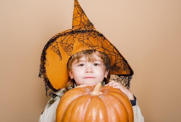 ハロウィーンのカボチャジャックoランタンのトリックまたは御馳走を抱き締める魔女の帽子の幸せなハロウィーンのかわいい男の子
