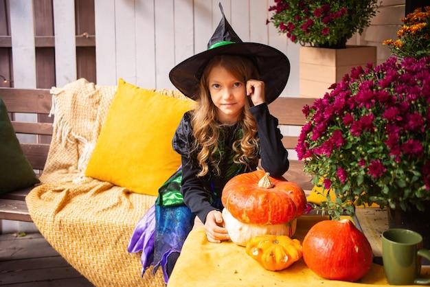 ハッピーハロウィンかわいい笑う魔女の衣装を着た少女がハロウィーンを祝う