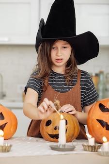 Счастливый хэллоуин милая маленькая девочка в костюме ведьмы с резьбой по тыкве счастливая семья готовится к хэллоуину. девушка зажигает свечи