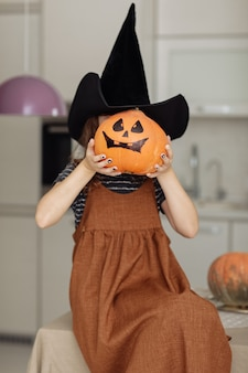 Happy halloween. cute little girl in witch costume with carving pumpkin. happy family preparing for halloween. focus on the pumpkin.