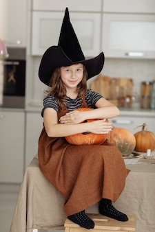 Happy halloween. cute little girl in witch costume with carving pumpkin. happy family preparing for halloween.